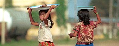Dos niñas caminan por una calle de Phnom Penh. (AP/Andy Eames)