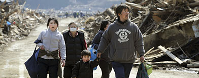 Survivors walk through a devastated urban area in Minami Sanriku, Miyagi, northern Japan. (AP Photo/Kyodo News)