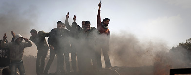 Libyan rebels celebrate on top of burning cars after Libyan leader Moammar Gadhafi's forces were pushed back from Benghazi, eastern Libya, Saturday, March 19, 2011.