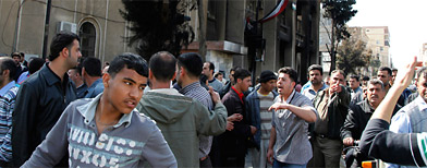 People gather outside the main courthouse in the southern Syrian city of Deraa. (Khaled al-Hariri/Reuters)