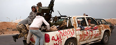 Libyan rebels jump onto the back of their vehicle as they leave Ras Lanouf, 250 km east of Sirte, central Libya, Tuesday, March 29, 2011. (Anja Niedringhaus/AP Photo)
