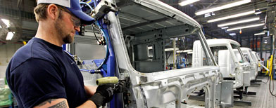 A worker with an American Flag tattoo works on a cab frame on the Volvo truck assembly line at the Volvo plant in Dublin, Va. (AP Photo/Steve Helber)