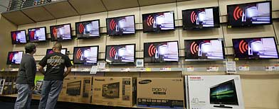 In this April 6, 2011 photo, people shop for televisions at a Best Buy in Glendale, Calif. Consumers spent more in March on furniture, electronics and at restaurants, but also paid more for gas.(AP Photo/Damian Dovarganes)