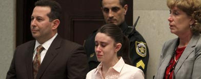 Casey Anthony holds hands with her defense attorneys, Jose Baez, left, and Dorothy Clay Sims, as they listen to the verdict at the Orange County Courthouse in Orlando, Fla., Tuesday, July 5, 2011. The jury acquitted Anthony of murdering her daughter, Caylee. (AP Photo/Red Huber, Pool)