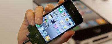 Man with iPhone at a Verizon store. (AP Photo/Amy Sancetta)