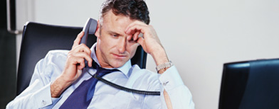(Businessman sitting at desk using phone, resting head on hand/Thinkstock/Digital Vision)