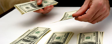 Person counting bills (Thinkstock)