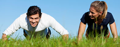 Man and woman exercising in the park. (ThinkStock)