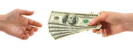 Large dollar bills exchanging hands (Thinkstock)