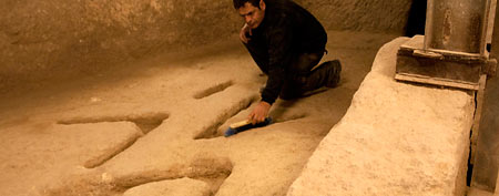 Archeologist Eli Shukron sweeps marks carved in the bedrock near Jerusalem's Old City. (AP/Sebastian Scheiner)