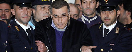 Italian policemen escort fugitive mobster Michele Zagaria, center, at the police headquarters in Naples, Southern Italy, Wednesday, Dec. 7, 2011. (AP Photo/Salvatore Laporta)