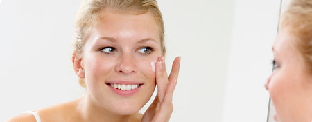 Woman applying skin lotion. (ThinkStock)
