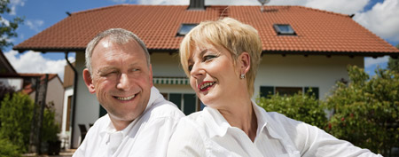 Retired couple in front of their home (ThinkStock)