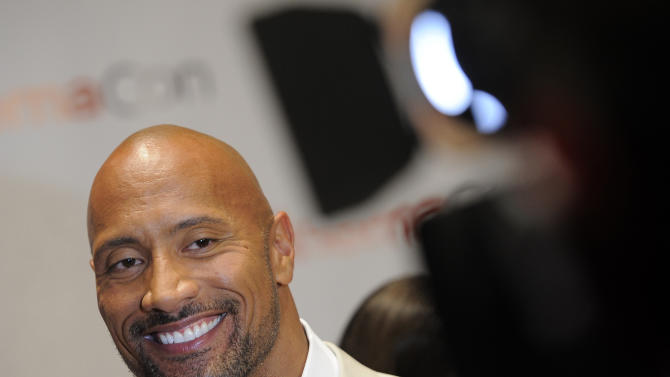 """FILE - Dwayne Johnson, a cast member in the upcoming film """"G.I. Joe: Retaliation,"""" smiles during an interview on the opening night of CinemaCon 2012, the official convention of the National Association of Theater Owners, in this April 23, 2012 file photo. (AP Photo/Chris Pizzello, File)"""