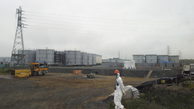 In this Wednesday, June 12, 2013 file photo, a construction worker walks beside the underground water tanks at the Fukushima Dai-ichi nuclear plant at Okuma in Fukushima prefecture, Japan. The operator of Japan's tsunami-crippled nuclear power plant said Tuesday, Aug. 20, 2013, that about 300 tons of highly radioactive water have leaked from one of the hundreds of storage tanks there - its worst leak yet from one of the vessels. (AP Photo/Toshifumi Kitamura, Pool)