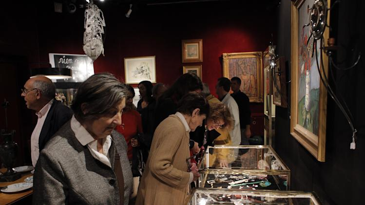 This Oct. 23, 2012 photo shows visitors inspecting jewels and paintings at the Drouot auction's house, in Paris. The famous auction house in Paris offers 16 functioning auctions rooms and is the world's largest auction house open to the public.  (AP Photo/Christophe Ena)