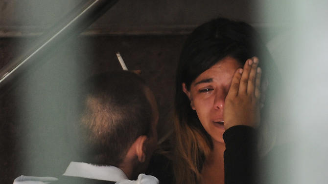 A woman cries after identifying the body of a loved one, who died in a commuter train crash, at the morgue in Buenos Aires, Argentina, Thursday Feb. 23, 2012.  Wednesday's commuter train crash killed dozens and sent hundreds to emergency rooms.  A federal judge was leading an investigation into what caused the rush-hour commuter train to slam into a barrier at the end of the track at a downtown station, crumpling cars around hundreds of riders. (AP Photo/Rodolfo Pezzoni, DyN)