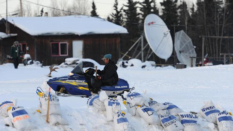 Iditarod drop bags caring supplies for the mushers are lined up along the Athabaskan village of Nikolai, Alaska, on Tuesday, March 5, 2013.  (AP Photo/Bill Roth, Anchorage Daily News)