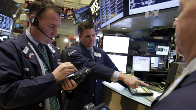 Specialist Todd Abrahall, center, works with traders on the floor of the New York Stock Exchange Friday, Dec. 21, 2012. Stocks opened sharply lower Friday on Wall Street after House Republicans called off a vote on tax rates and left federal budget talks in disarray 10 days before sweeping tax increases and government spending cuts take effect. (AP Photo/Richard Drew)