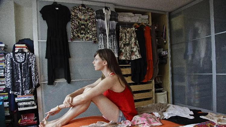 This Aug. 15, 2012 photo shows model Elettra Wiedemann posing on her bed among fashion from her closet at her apartment in New York.  Wiedemann, daughter of Isabella Rossellini, landed on this year's Vanity Fair's International Best-Dressed dressed list. She's now keeping company with the Duchess of Cambridge, Diane Kruger and Jay-Z.  (AP Photo/Bebeto Matthews)