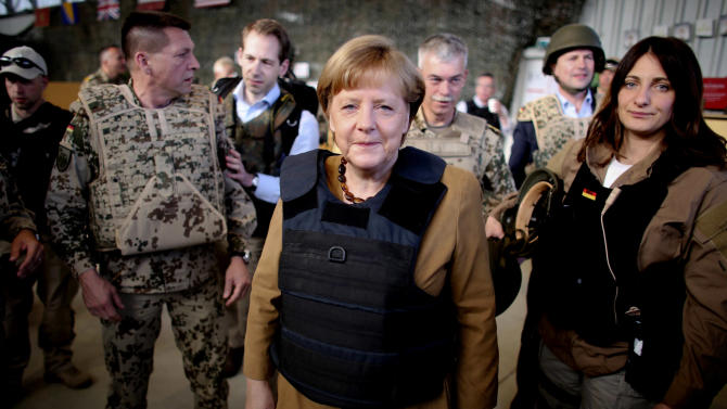 German Chancellor Angela Merkel, center,  is dressed in a bullet proofed vest as she arrives  to Mazar-e-Sharif, Afghanistan, Friday, May 10, 2013. Germany's Chancellor Angela Merkel made a surprise trip to northern Afghanistan to visit her troops less than two weeks after insurgents killed a German special forces soldier and wounded a second, a military spokesman said. Germany is the only NATO nation that is committed to leaving troops in Afghanistan after the coalition completes its scheduled pullout of combat forces next year. The U.S. is likely to deploy several thousand troops if the Afghan government provides them legal protection. (AP Photo/DPA/Kay Nietfeld)
