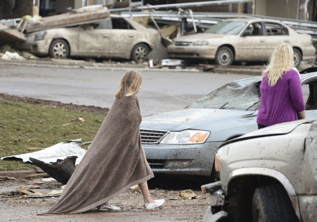 A girl walks, wrapped in a blanket, near the Moore Hospital after a tornado destroyed buildings and overturned cars in Moore
