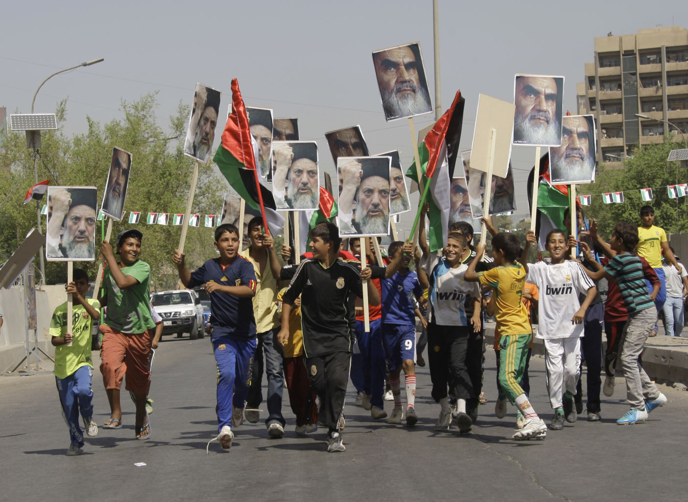 Children wave palestinian flags and hold posters of the late iraqi