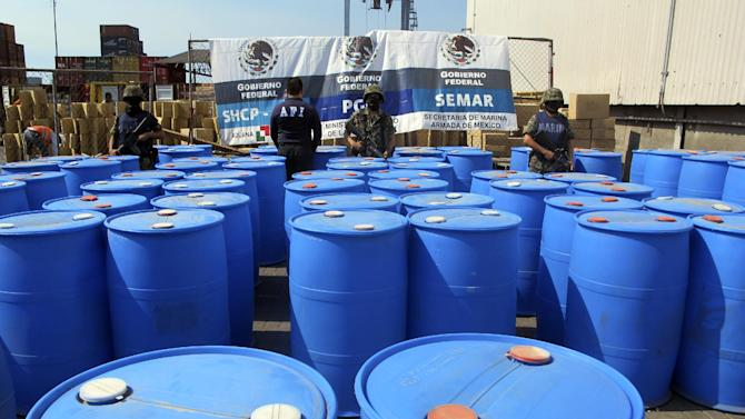 """In this photo released by the Mexican navy on Dec. 28, 2011, Navy marines stand guard in front of several barrels containing 120,000 kilograms of methylamine, a controlled substance used as a precursor to methamphetamine, that were inside several containers headed for Guatemala, seized at the Pacific port of Lazaro Cardenas, Mexico, Dec. 23, 2011. Based on seizure data, and interviews with U.S. and Guatemala officials, it appears that Sinaloa cartel chief Joaquin """"El Chapo"""" Guzman appears to be taking advantage of Guatemala's remote, isolated mountains and an alliance with a key Guatemalan trafficker to make the Central American nation into a new international meth production base. (AP Photo/SEMAR)"""