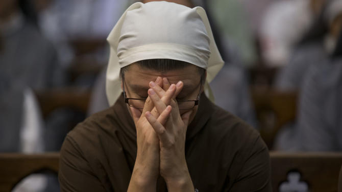 A nun clasps her hands in prayer during a Mass honoring Pope Benedict XVI at the Metropolitan Cathedral in Buenos Aires, Argentina, Wednesday, Feb. 27, 2013.  Benedict made his final public appearance as pontiff in St. Peter's Square Wednesday. He thanked his flock for respecting his retirement, which takes effect Thursday. (AP Photo/Natacha Pisarenko)