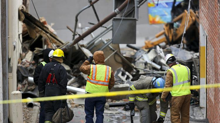 An ATF agent, second from right, looks down a hole in an alley near JJ's restaurant after an explosion and fire tore through the establishment Tuesday evening near the Country Club Plaza Wednesday, Feb. 20, 2013, in Kansas City, Mo. The fire killed one person and injuring over a dozen. (AP Photo/Ed Zurga)