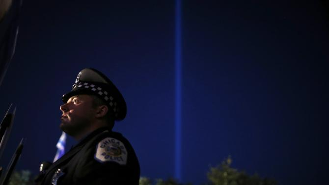 A beam of light is projected into the sky as a Chicago Police officer attends the 11th Annual Chicago Police Memorial Foundation's Candlelight Vigil in Chicago