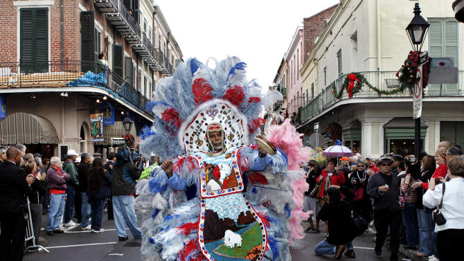 """FIE - In this Jan. 1, 2008 file photo, """"Big Chief"""" Alfred Doucette, dances in a parade on Royal Street in the French Quarter of New Orleans. When the Mardi Gras Indians take to the street the elaborate beads and waving feathers will stop traffic and start the cameras clicking. Now they hope that when those taking pictures of them and their suits resell them, they will be in line for some of that profit. Ashlye Keaton, an adjunct law professor at Tulane, has been working with the Mardi Gras Indians to help them copyright their costumes.  (AP Photo/Judi Bottoni, File)"""