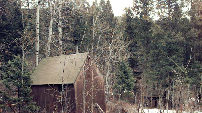 """FILE - In this April 6, 1996 file photo, the cabin of Unabomber Theodore Kaczynski, partially surrounded by white, plastic tape, sits at the end of a muddy, private road, hidden in a wooded setting about 300 yards from the nearest neighbor in Lincoln, Mont. The 1.4-acre parcel of land in western Montana that was once owned by Kaczynski is on the market for $69,500. The listing offers potential buyers a chance to own a piece of """"infamous U.S. history"""" and says the forested land """"is obviously very secluded. (AP Photo/Elaine Thompson, File)"""