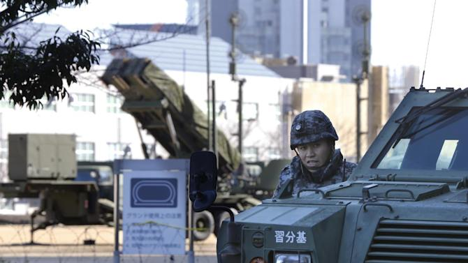 A member of the Japan Self-Defense Forces stands near a PAC-3 Patriot missile unit, background, deployed for North Korea's rocket launch at Defense Ministry in Tokyo, Sunday, Feb. 7, 2016. North Korea on Sunday defied international warnings and launched a long-range rocket that the United Nations and others call a cover for a banned test of technology for a missile that could strike the U.S. mainland. (AP Photo/Shizuo Kambayashi)
