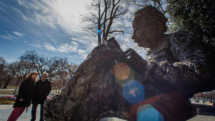 Joy Michelson and Richard Clancy of Canaan, N.H. look at the the statue of Albert Einstein near the National Academy of Sciences building in Washington, Thursday, March 14, 2014. Today is the 135th anniversary of Einstein's birth. (AP Photo/J. David Ake)