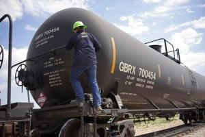 A worker climbs onto a crude oil train to set the handbrake at the Eighty-Eight Oil LLC's transloading facility in Ft. Laramie