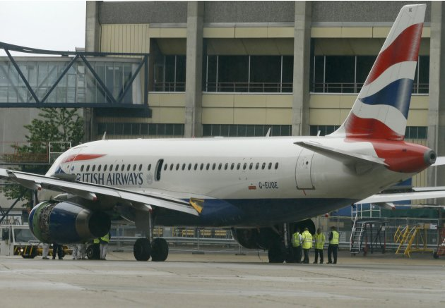 Workers look at a British Airways passenger jet after it was towed off the runway following an emergency landing at Heathrow Airport west of London
