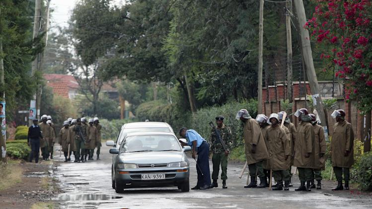 Riot police stop cars to check as they patrol a street in Nairobi, Kenya Friday, March 8, 2013. The leading candidate in the race for Kenya's president is hovering around the 50 percent mark as ballots are counted on what officials say is the last day of the count.  The election commission said it expected to have final results by the end of Friday, though observers said it was still possible the count would go into the weekend. (AP Photo/Sayyid Azim)