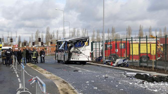 French police and officials work at the scene near the wreckage of a school minibus after it crashed into a metal panel which fell from a truck in Rochefort