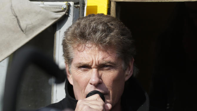 "US actor David Hasselhoff speaks to the crowed from a truck as he attends a protest against the removal of a section of the East Side Gallery, a historic part of the former Berlin Wall, in Berlin, Sunday, March 17, 2013. Hasselhoff is fondly remembered by many Germans for releasing a song called ""Looking for Freedom"" shortly before the fall of the Wall in 1989. (AP Photo/Markus Schreiber)"