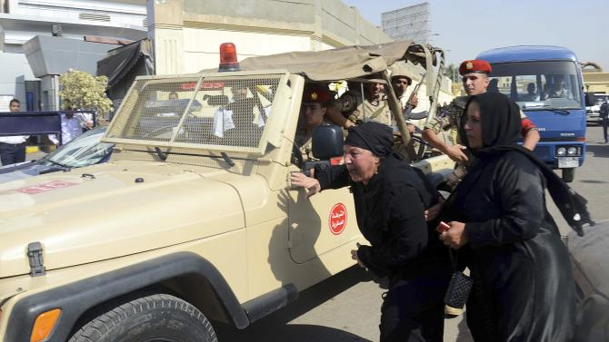 Family members of security forces killed in Sinai on Friday react near an army vehicle as they wait for the bodies of their relatives at Almaza military airbase in Cairo