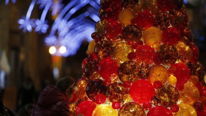 Girl looks at a Christmas tree made of glass baubles in Valletta