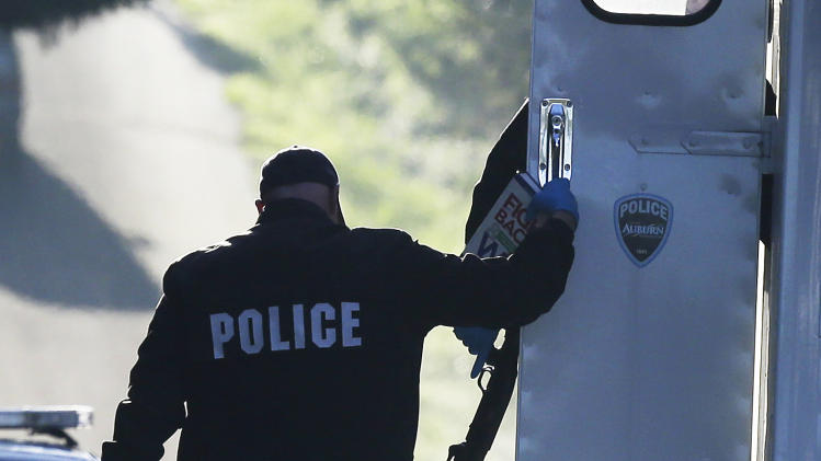 """Police officers carry a shotgun, a dictionary, and a copy of the Reader's Digest book """"Fight Back and Win: What to Do When You Feel Cheated or Wronged"""" as they collect evidence from the scene of an overnight shooting that left five people dead, including a suspect who was shot by arriving officers, police said early Monday, April 22, 2013, at an apartment complex in Federal Way, Wash. Federal Way Police Cmdr. Kyle Sumpter confirmed Monday that the shotgun pictured was used by the suspect in the shooting.(AP Photo/Ted S. Warren)"""