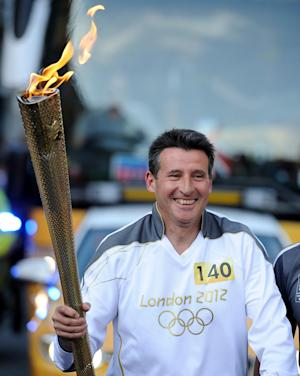 Torchbearer 140 Lord Sebastian Coe carries the Olympic Flame on the Torch Relay leg through Sheffield, England, Monday June 25, 2012. (AP Photo/PA, Ben Birchall) UNITED KINGDOM OUT  NO SALES  NO ARCHIVE