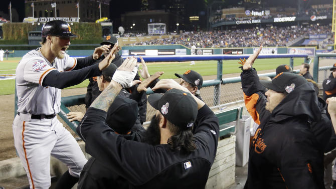 San Francisco Giants' Hunter Pence is congratulated in the dugout after scoring on a triple by Gregor Blanco during the second inning of Game 3 of baseball's World Series against the Detroit Tigers Saturday, Oct. 27, 2012, in Detroit. (AP Photo/David J. Phillip)