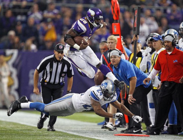 Minnesota Vikings running back Peterson leaps over Detroit Lions safety Coleman during the second half of their NFL football game in Minneapolis