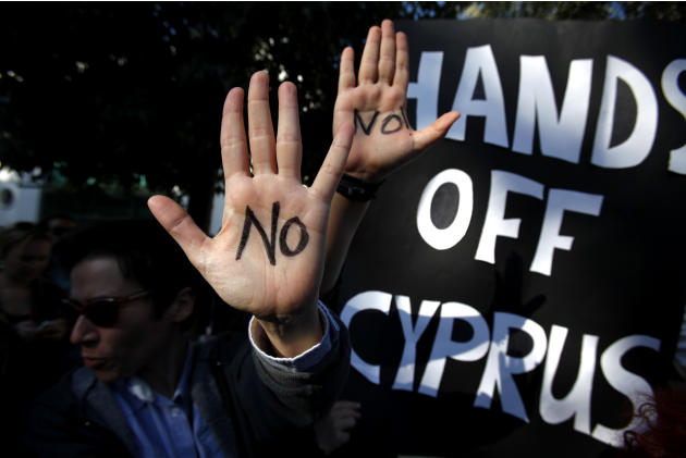 Protesters hold up their hands as they protest outside the parliament in capital Nicosia, Cyprus, Monday, March 18, 2013. A vote on a bailout package for Cyprus that includes an immediate tax on all s