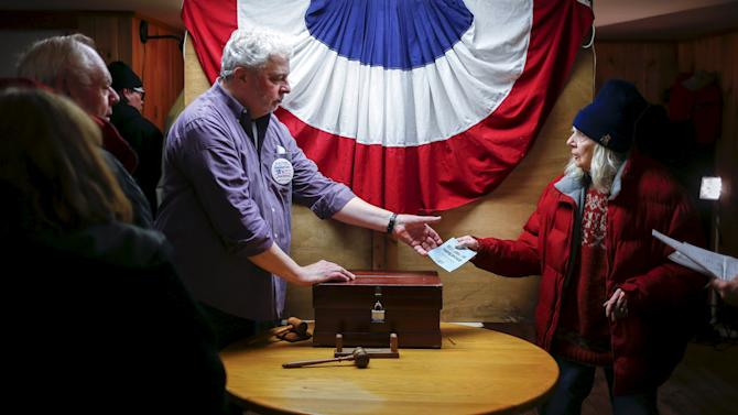 Resident Nancy Holmes, 77, hands her ballot to town moderator Leslie Schoof as she votes in New Hampshire's first-in-the-nation primary at the town hall in Hart's Location
