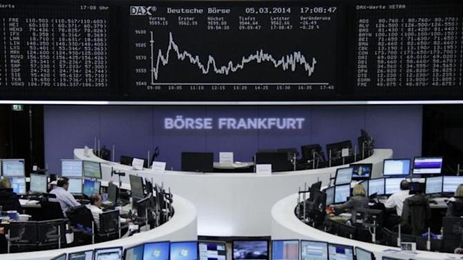 Traders are pictured at their desks in front of the DAX board at the Frankfurt stock exchange March 5, 2014. REUTERS/Remote/Fabrizio Bensch