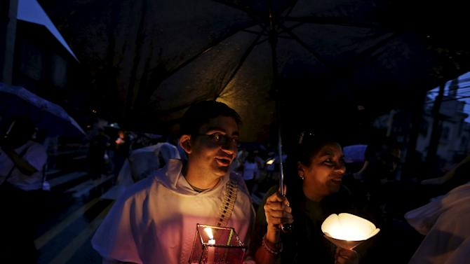 A priest and a woman hold candles during a procession for the late archbishop of San Salvador Oscar Arnulfo Romero in San Salvador